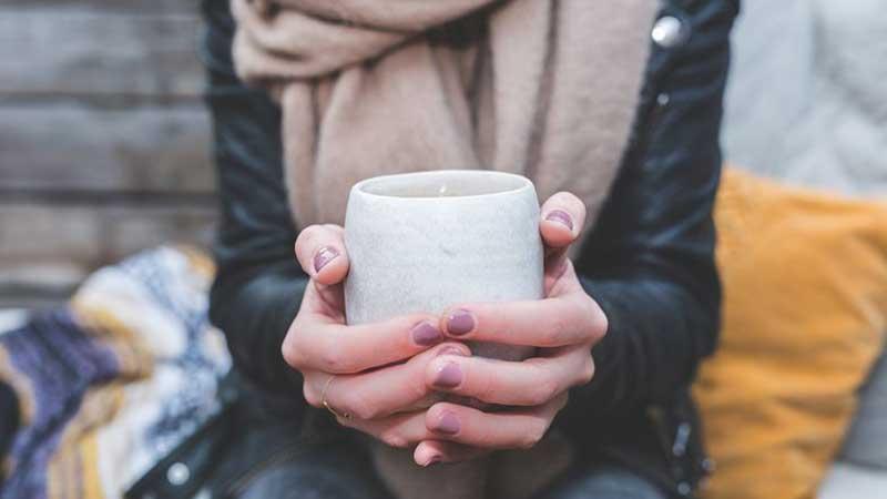 Hands holding coffee mug