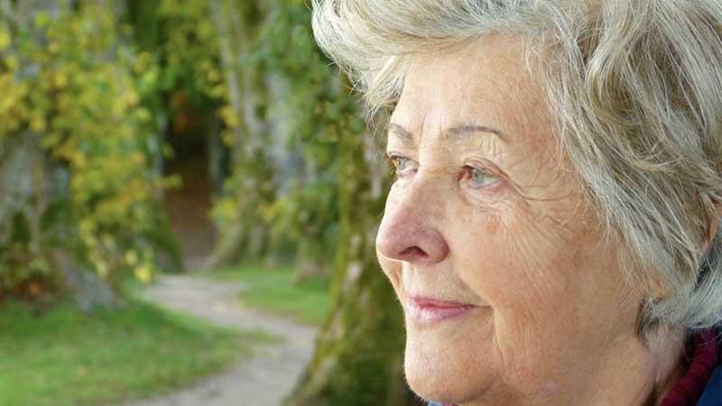 Elderly lady looking out window