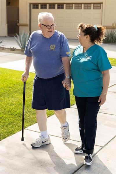 caregiver walking senior with cane