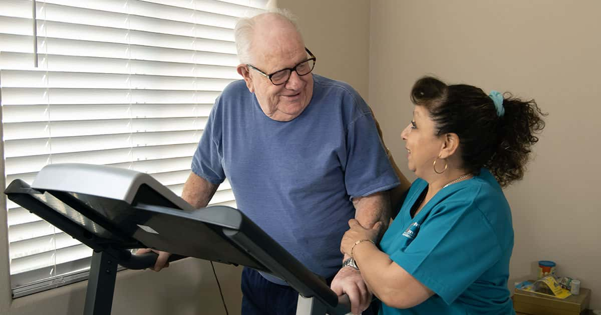caregiver helping senior walk on treadmill