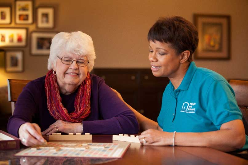 senior playing scrabble with caregiver