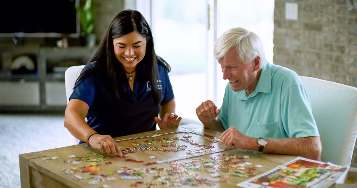 caregiver and senior putting together a puzzle