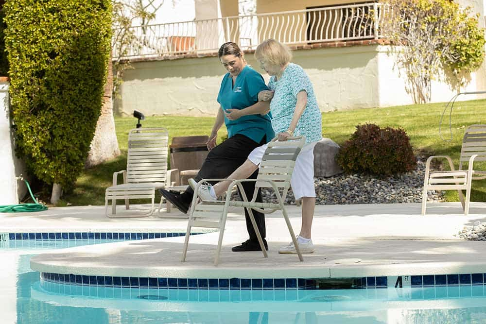 Caregiver exercising with senior by swimming pool