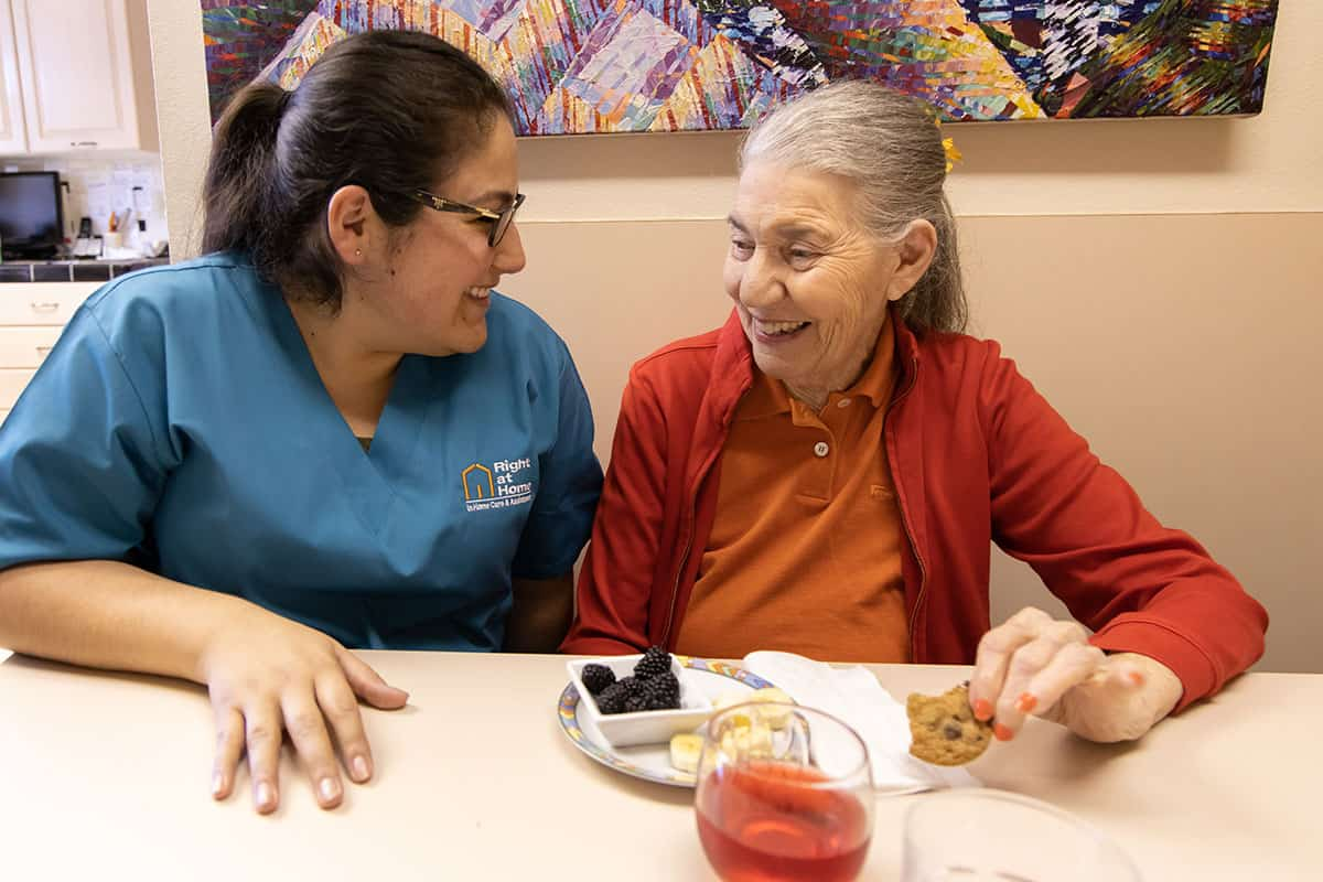 caregiver and senior having snack