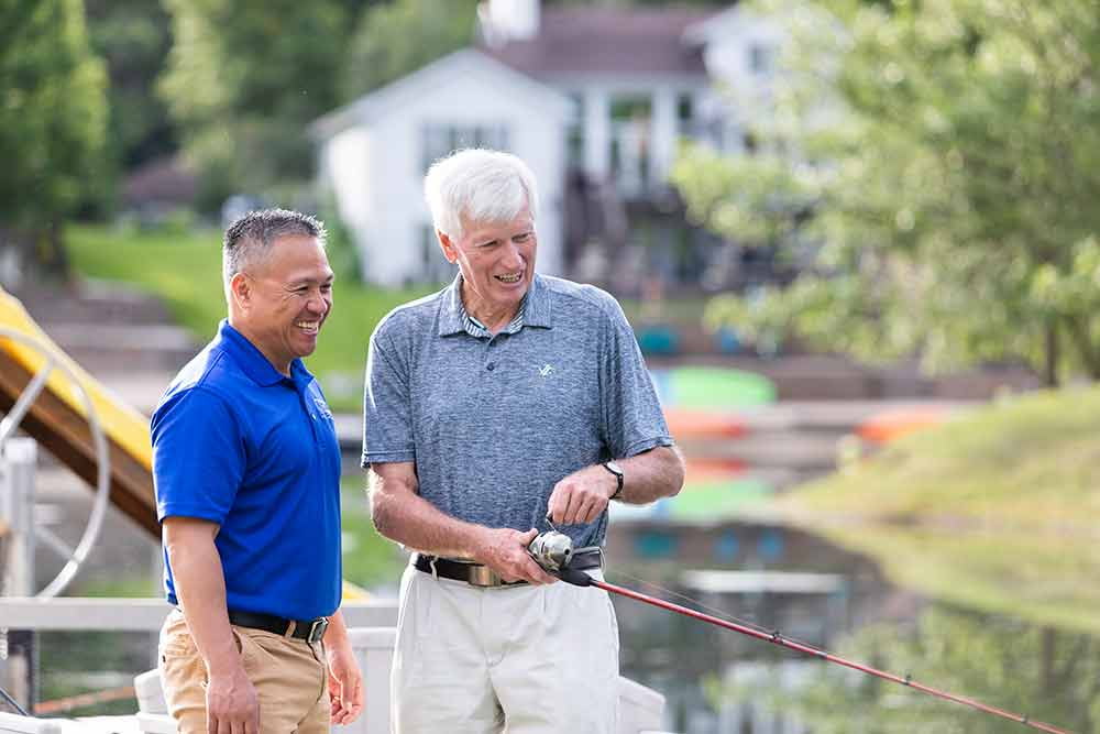 Senior and Caregiver fishing