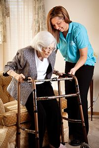 Caregiver Assists Senior with Standing