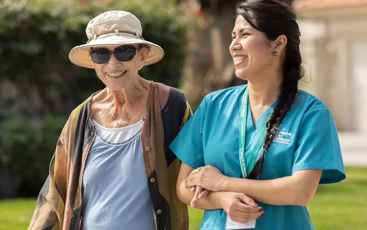 caregiver walking outside with senior