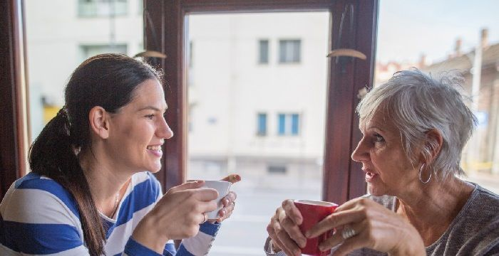 Nursing Student with Elderly Woman Drinking Out of Mugs