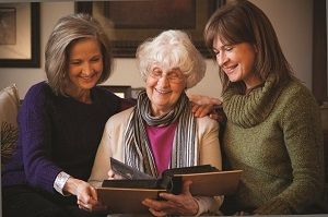 Senior and Female Family Members wearing Sweaters Reading Book Together