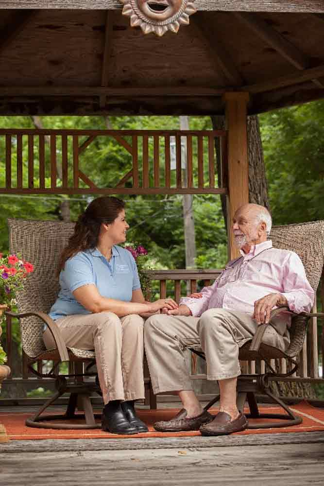 caregiver with senior outside under gazebo