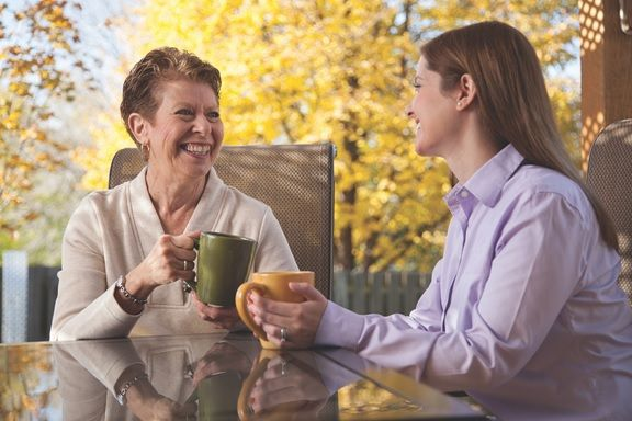 Caregiver and Senior Enjoying a Beverage Together While Seated Outside at Table Surrounded by Fall Trees