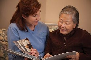 Right at Home Caregiver Looking at Photo Album with Senior Woman at Home