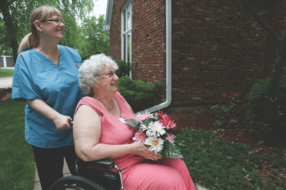 Caregiver in Blue Scrubs Walking with Elderly Woman in Wheelchair Holding Flowers