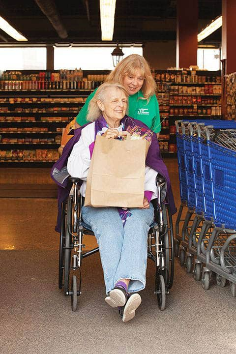 Grocery shopping, caregiver pushing senior in wheelchair