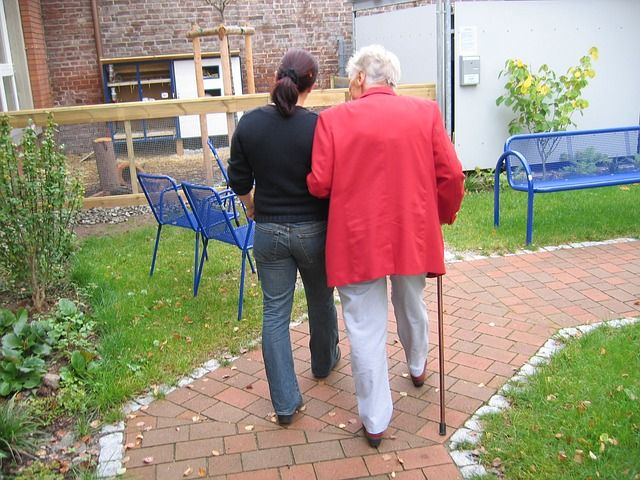 Right at Home Caregiver Walking with Female Client on Brick Path Outside Building Near Park Benches