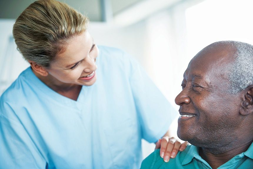Right at Home Caregiver in Blue Scrubs Standing Next To Male Senior Client