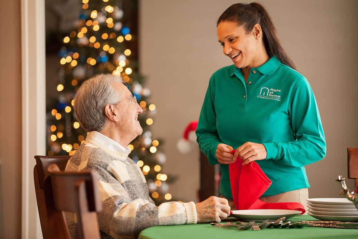 caregiver serving senior dinner during holidays