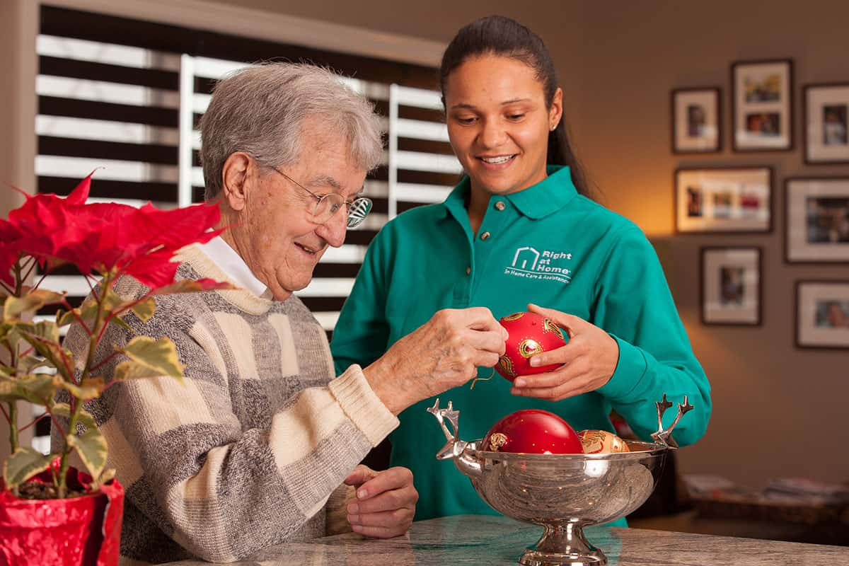 caregiver and senior with holiday decorations
