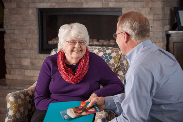 Senior woman wearing purple sweater and red scarf meeting Right at Home care coordinator