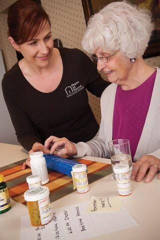 Right at Home Caregiver Standing With Female Senior Client Checking Medications