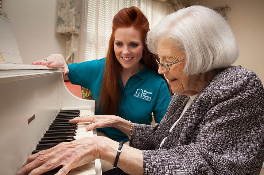 Senior playing piano with caregiver