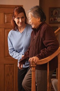 Right at Home Caregiver Assisting Senior Woman in Safely Descending Stairs