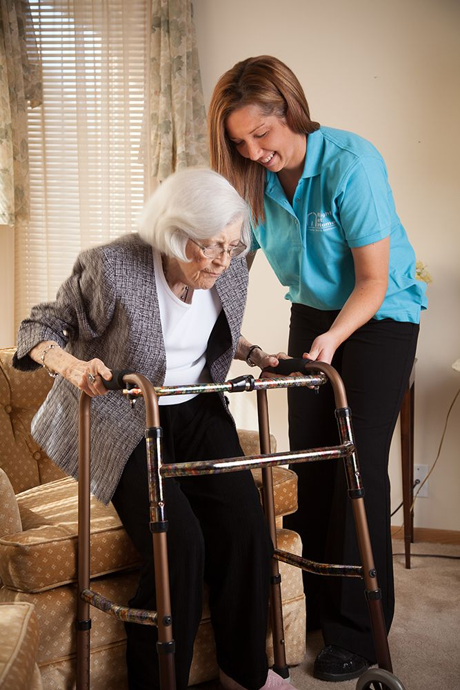 Transition Care, helping senior client stand with walker after surgery