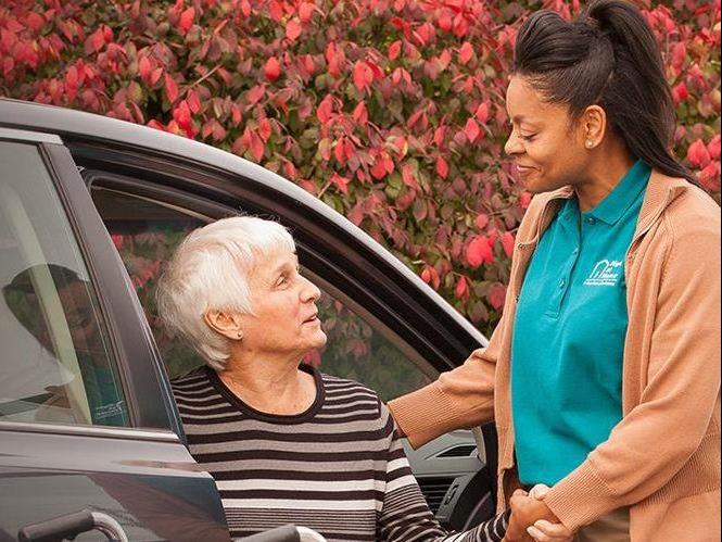 Caregiver helping senior out of car.