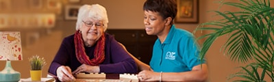Caregiver with senior at table