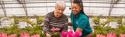 senior picking out flowers with caregiver