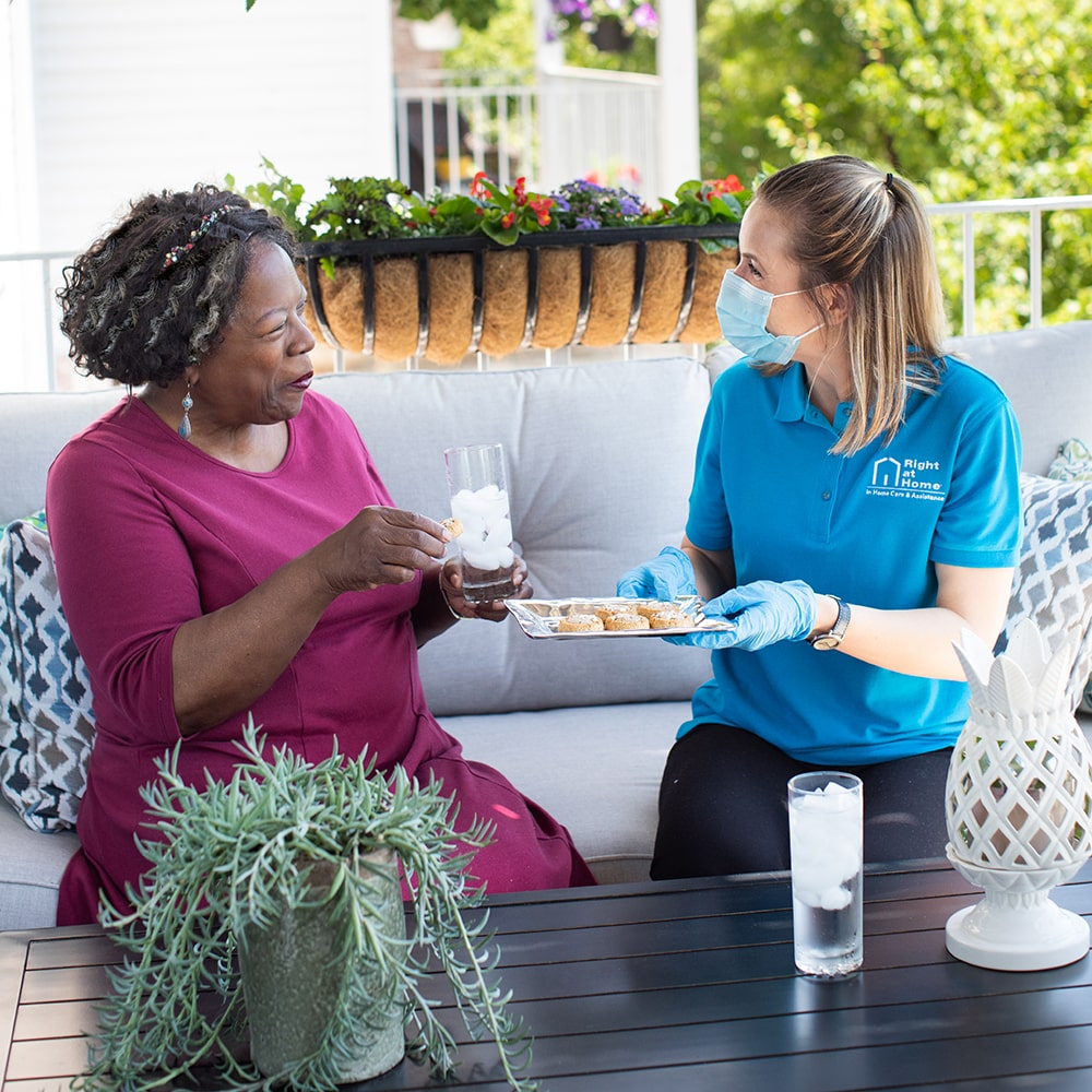 Caregiver wearing PPE spending companionship time with senior client