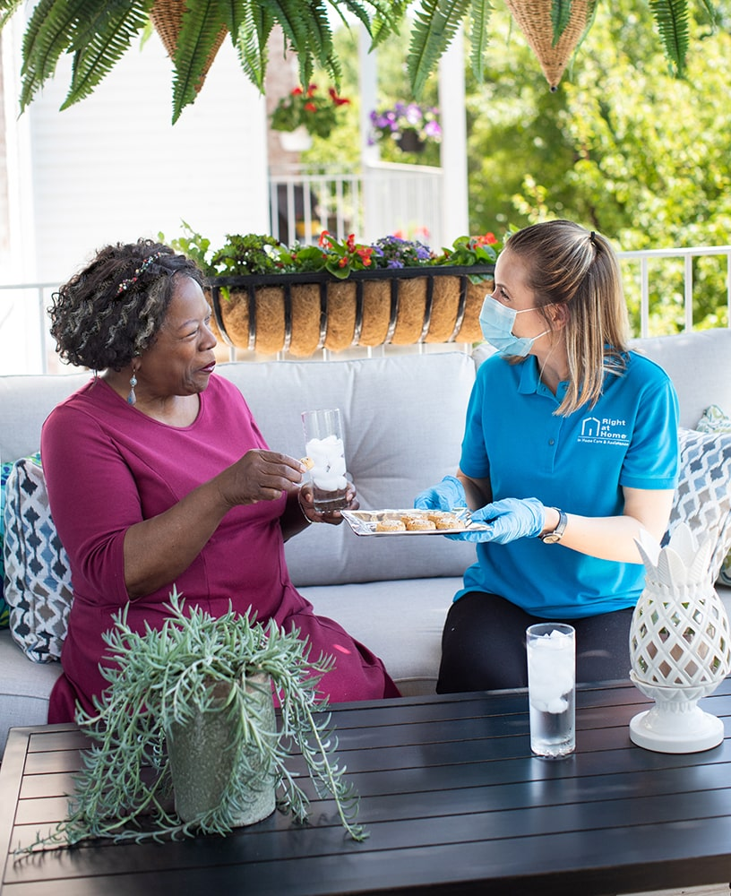 Caregiver wearing PPE sitting outside with senior client