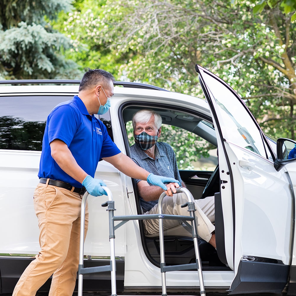 Caregiver wearing PPE assisting senior client out of the car