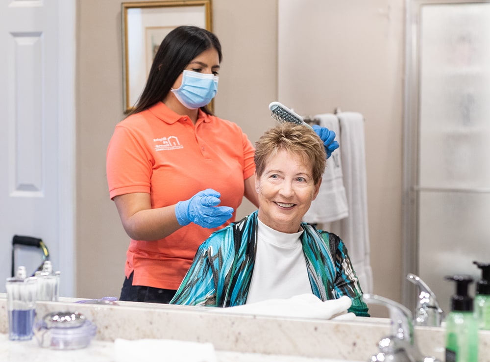Caregiver wearing PPE assisting senior client with hair grooming