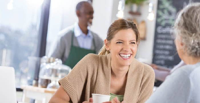 female in coffee shop, smiling at person she is talking to