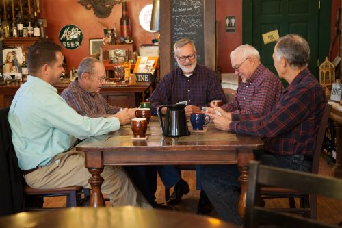 five men playing cards drinking coffee
