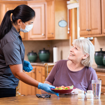 Caregiver Serving a Meal to a Senior Client