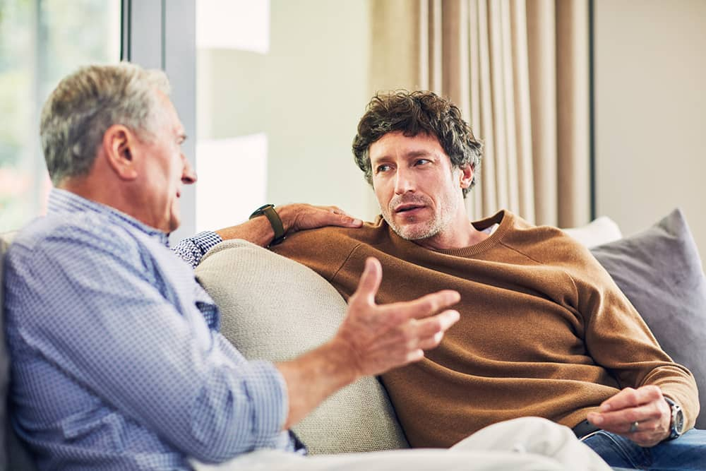 Adult son sitting on couch with senior dad in discussion