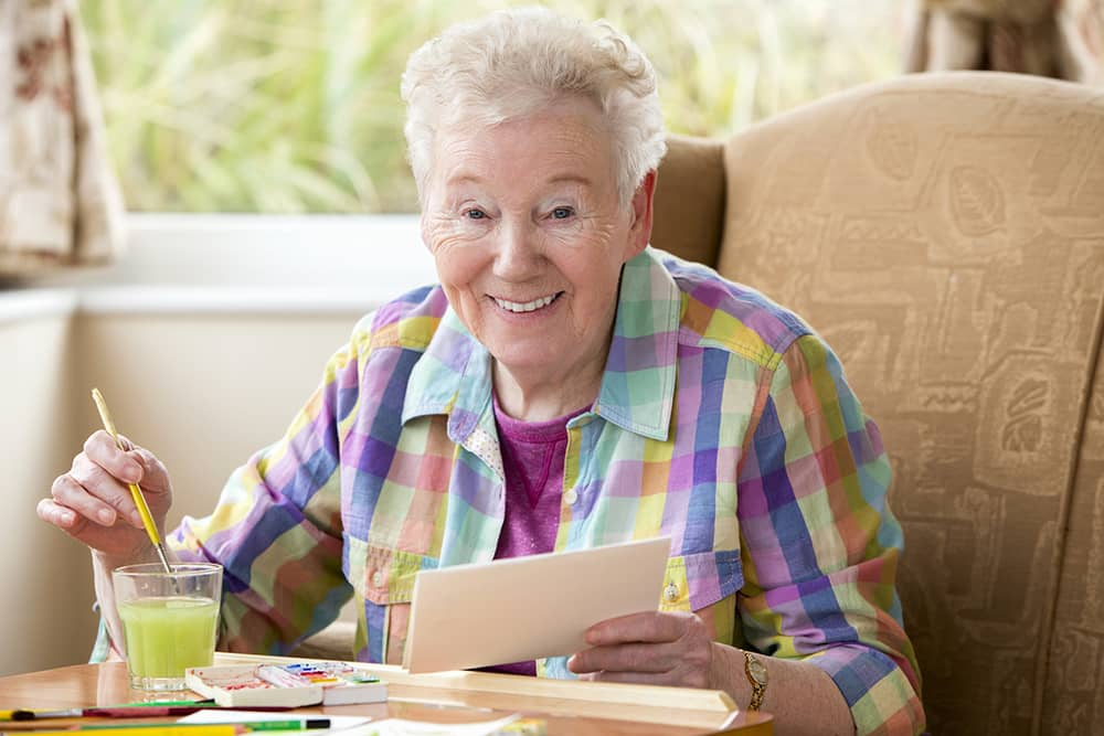 Senior woman painting a postcard and smiling