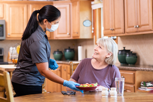 Female Right at Home Caregiver in PPE serving food to a female senior