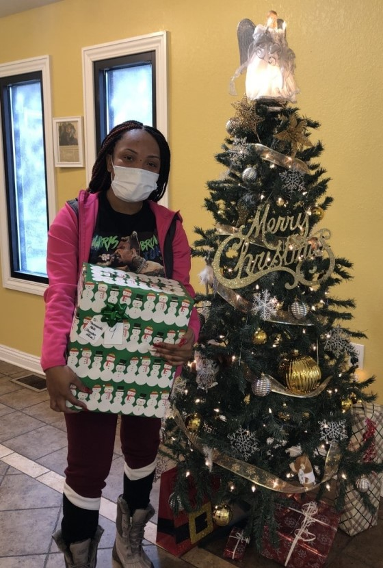 Caregiver Shawanda Hale receives a gift by the Christmas tree.