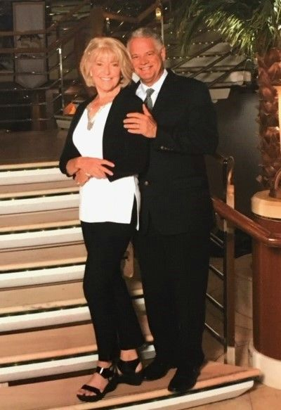 Mark and Elaine Wimbush dressed up standing and posing on stairs