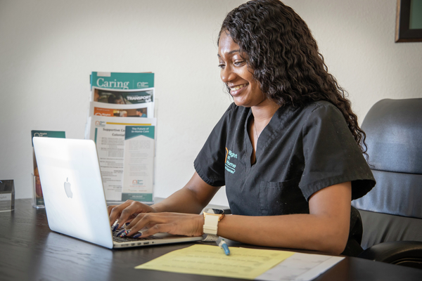 African American woman in scrubs typing on a laptop at a table
