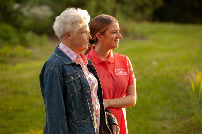 Female senior with female caregiver in field