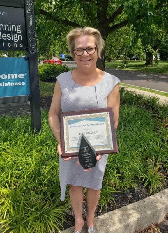 Cindy Urzillo proudly displays her Selfless Heart Service Award