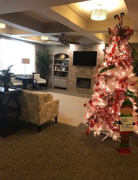 Elf Themed Red and White Christmas Tree Decorated by Right at Home at Celebration Village Acworth