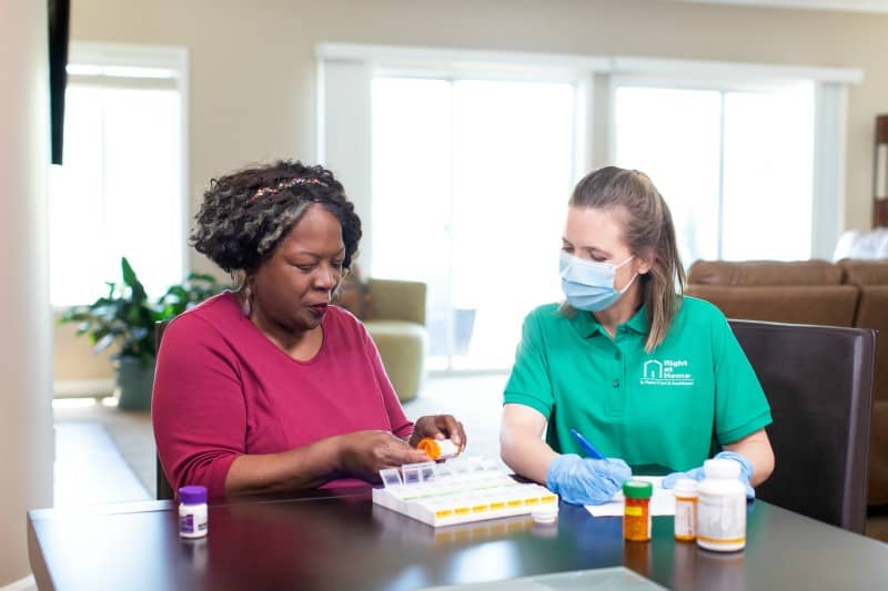 Personal caregiver with client sorting medications