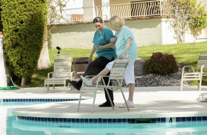 Female caregiver helping female senior exercise next to a pool