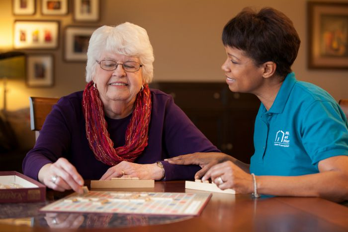 senior and caregiver playing scrabble