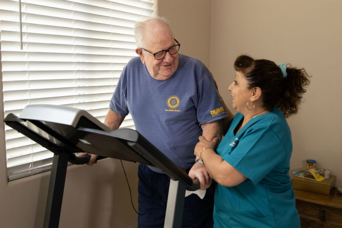 senior male on treadmill with assistance from a female caregiver